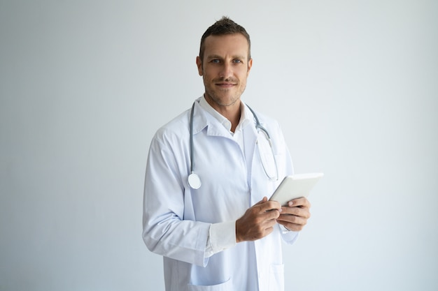 Pozytywny ufny młody lekarz praktykujący używa cyfrowego przyrząd przy pracą.