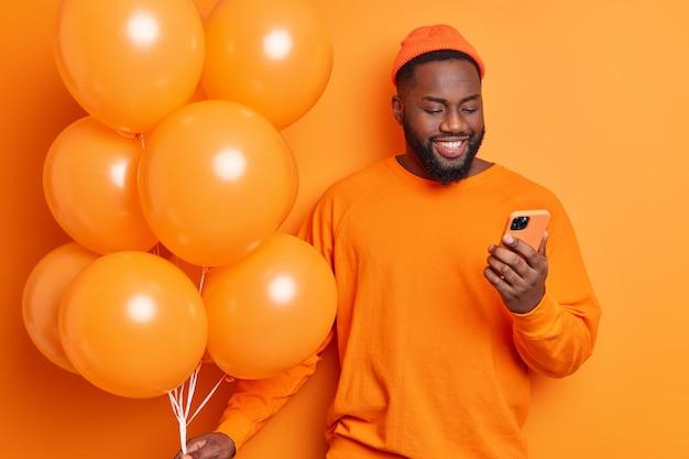 Pozytywny urodzinowy facet otrzymuje wiadomości z gratulacjami na smartfonie świętuje rocznicę ubrany w sweter i kapelusz w pozach z balonami czeka, aż goście przyjdą na przyjęcie odizolowane na pomarańczowej ścianie