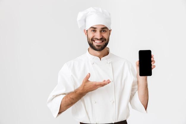 Pozytywny uśmiechający się młody kucharz pozowanie w mundurze trzymając telefon komórkowy pokazując pusty wyświetlacz.