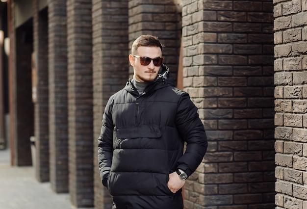 Pozytywny Uśmiechnięty Młody Mężczyzna W Stylowych Ubraniach Stojący Samotnie Na Zewnątrz W Pobliżu ściany Miejskiego Budynku I Mówiący Przez Telefon Komórkowy Premium Zdjęcia