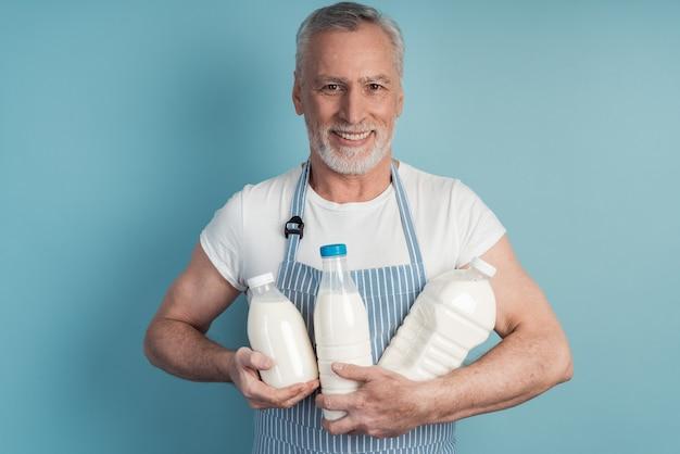 Pozytywny, uśmiechnięty, starszy mężczyzna trzyma butelkę mleka na niebieskiej ścianie na białym tle