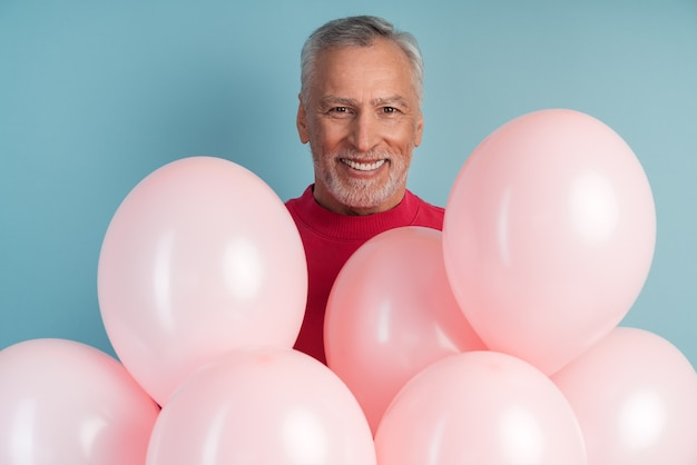 Pozytywny, wesoły człowiek z balonów, pozowanie na niebieskiej ścianie