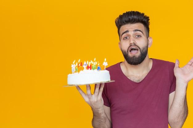 Pozytywny zabawny młody facet z czapką i płonącą świeczką i domowym ciastem w rękach pozuje