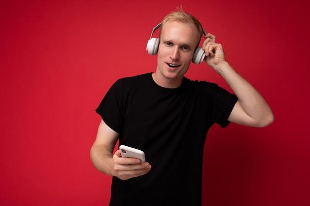 Pozytywny zachwycający przystojny blondyn młody człowiek ubrany w czarny t-shirt i stojących białych słuchawek