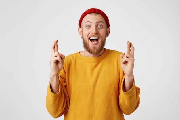 Pozytywny zadowolony brodaty mężczyzna krzyżuje palce