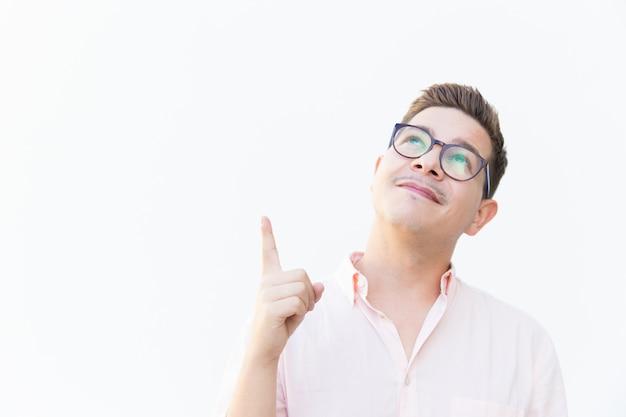 Pozytywny zadumany facet wskazuje palec w okularach
