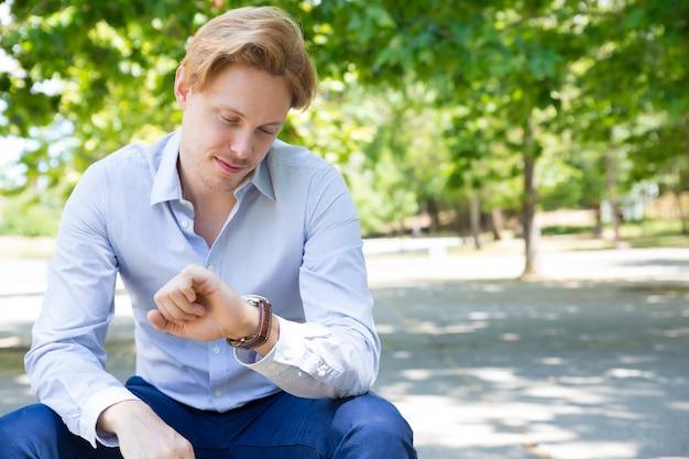 Pozytywny zadumany faceta czekanie na dziewczyny w parku