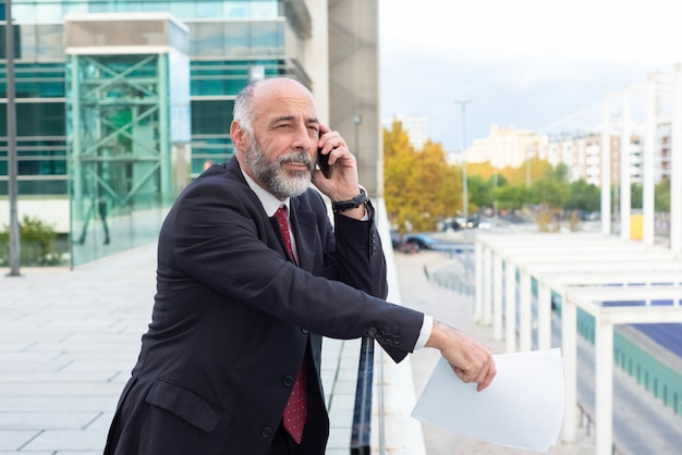 Pozytywny zadumany szary z włosami biznesmen opowiada na telefonie komórkowym