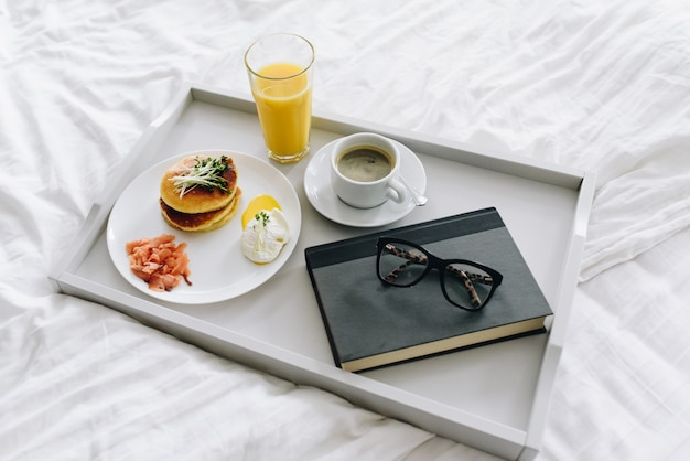 Pożywne i smaczne śniadanie w łóżku na tacy z kawą, sokiem pomarańczowym, szklankami i książką