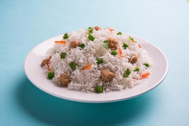 Pożywny sojowy pulao lub pilaf lub smażony w kawałkach sojowy ryż z zielonym groszkiem i fasolą. podawane w misce na kolorowym lub drewnianym tle. selektywne skupienie