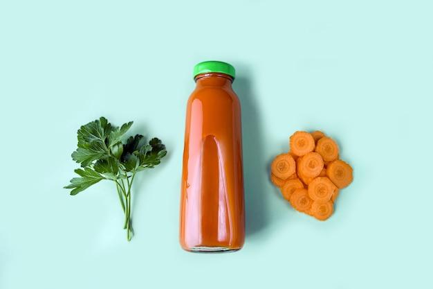 Pożywny sok marchwiowy detoksykacyjny w szklanej butelce. pojęcie diety alkalicznej. organiczny napój wegetariański i świeże marchewki na niebieskim tle