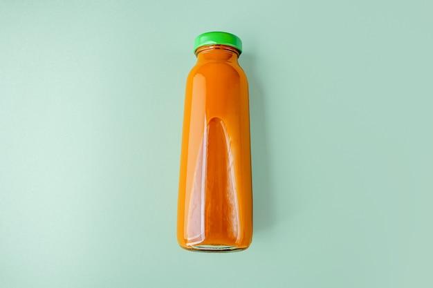 Pożywny sok z marchwi lub dyni w szklanej butelce. pojęcie diety alkalicznej. organiczny napój wegetariański na zielonym tle