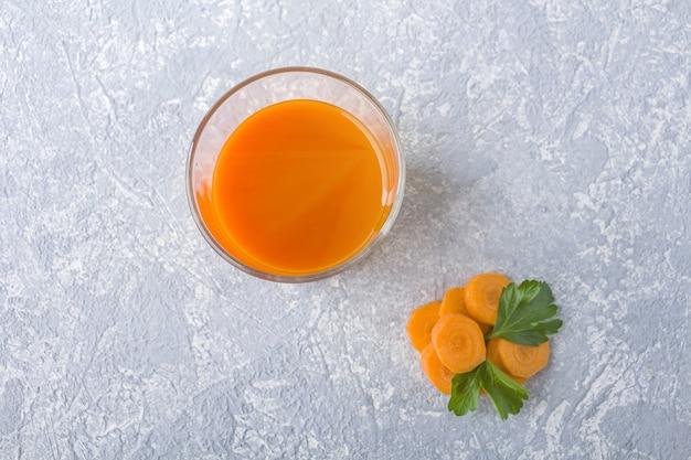 Pożywny sok z marchwi o właściwościach detoksykujących w szklance i liściach pietruszki. pojęcie diety alkalicznej. organiczny napój wegetariański
