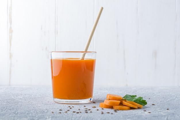 Pożywny sok z marchwi o właściwościach detoksykujących w szklance z siemieniem lnianym i liśćmi pietruszki. dieta alkaliczna