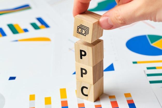 Ppc pay per click na drewnianych blokach z wykresami.