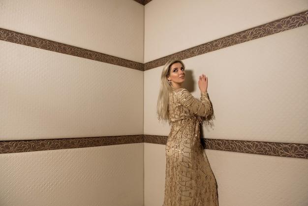 Pportrait piękna plus wielkości kędzierzawa młoda blond kobieta pozuje w kącie pokój.