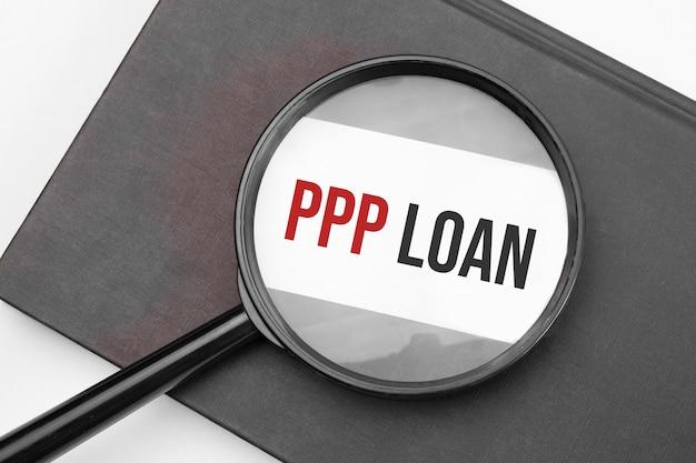 Ppp loan słowo na papierze przez szkło powiększające.