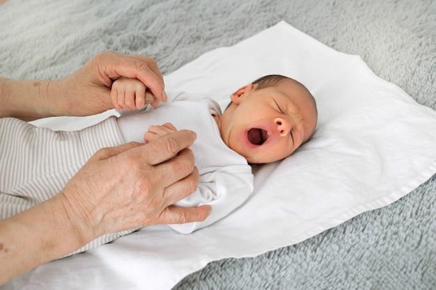 Prababka trzyma w ramionach nowonarodzoną wnuczkę