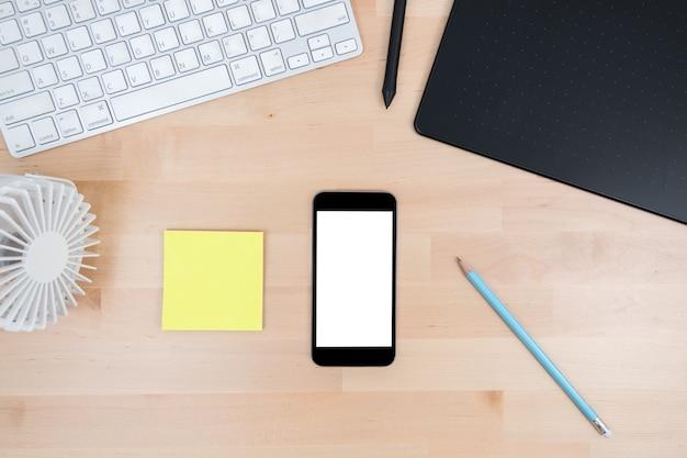 Praca biurowa drewniany stół z smartphone makiety.