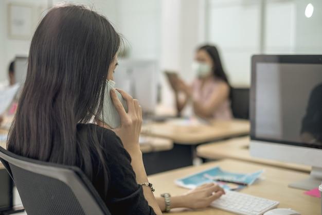 Praca biznesowa w biurze z kwarantanną dystansu społecznego w masce na twarz podczas wpływu covid19