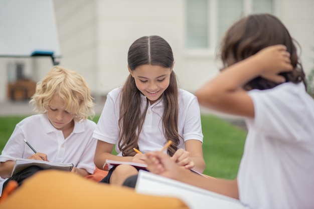 Praca domowa. dzieci w białych koszulach siedzą i uczą się razem