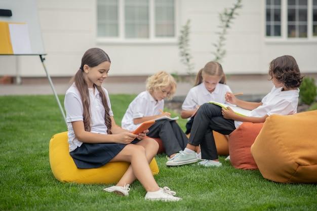 Praca domowa. dzieci w wieku szkolnym siedzą razem na torbach i wyglądają na zaangażowanych