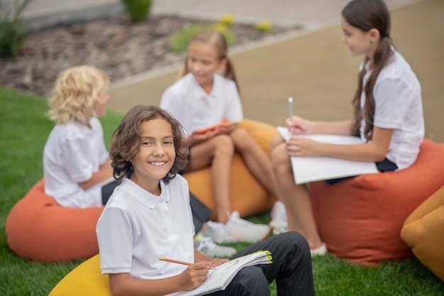 Praca domowa. uczniowie siedzą razem na torbach i omawiają prace domowe