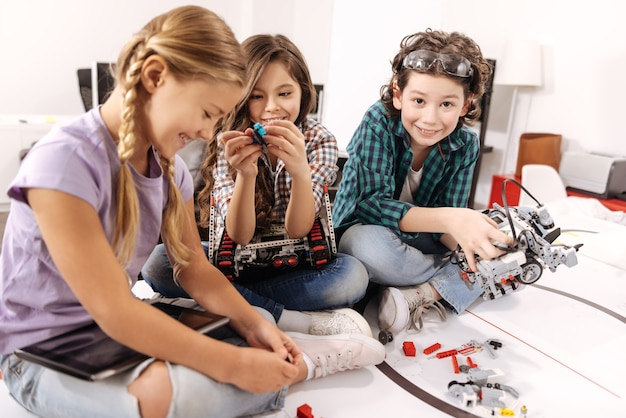Praca drużynowa. uśmiechnięte zadowolone i szczęśliwe dzieci siedzące w klasie naukowej i wyrażające radość używające gadżetów i urządzeń
