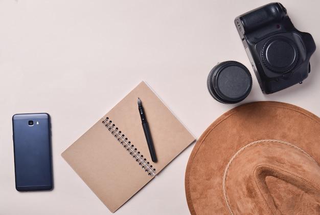 Praca fotoreportera. smartfon, notatnik, kapelusz, aparat fotograficzny, obiektyw. koncepcja podróży, widok z góry, płaskie świeckich