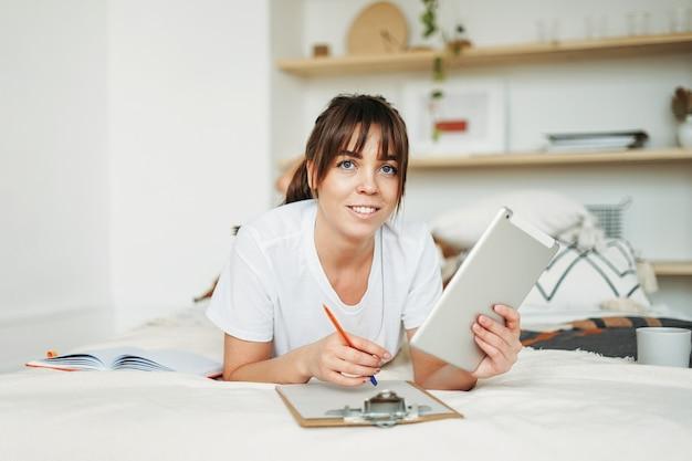 Praca freelancer młoda brunetka kobieta z tabletem pracy na łóżku w domu w jasnym wnętrzu