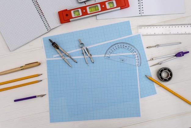 Praca inżyniera z papierem milimetrowym i sprzętem do rysowania