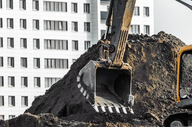 Praca koparki na ziemi na tle domów wielopiętrowych.