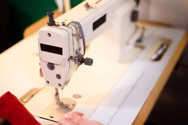 Praca krawiecka na stanowisku pracy w atelier. maszyna do szycia, linijka, nożyczki, lampa stołowa, nici na tle.