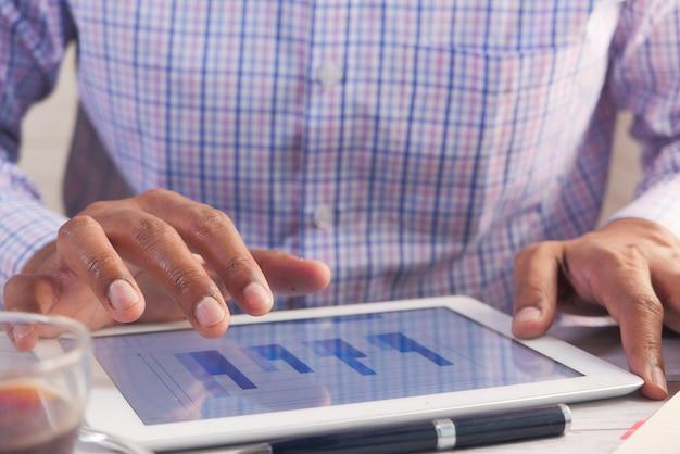 Praca na cyfrowym tablecie przy biurku przy użyciu samodzielnie utworzonego wykresu