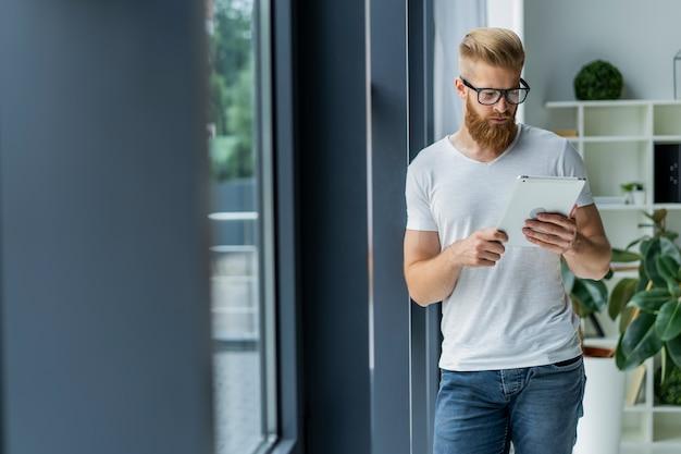 Praca na nowym tablecie. niski kąt widzenia pewnie młody człowiek pracujący na cyfrowym tablecie, stojąc przed dużym oknem w biurze lub kawiarni.