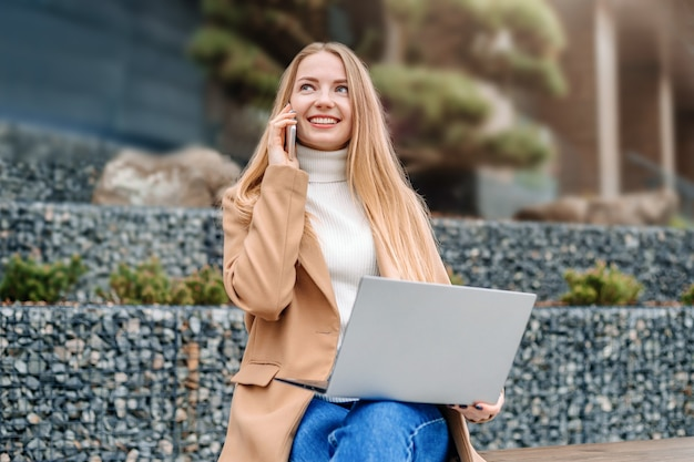Praca na odległość. biznesowa młoda blondynka siedzi na ławce z telefonem komórkowym i laptopem, rozmawiając i pracując
