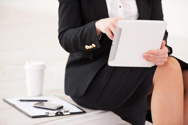 Praca na tablecie cyfrowym. przycięty obraz bizneswoman siedzącej przy schodach i pracującej na cyfrowym tablecie