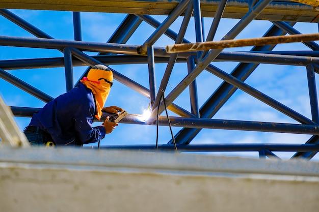 Praca na wysokości, man spawania konstrukcji dachu fabryki w budowie