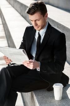 Praca na zewnątrz. młody biznesmen czyta gazetę siedząc na schodach