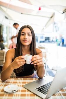 Praca na zewnątrz. piękna młoda kobieta w funky kapelusz działa na laptopie i uśmiecha się siedząc na zewnątrz