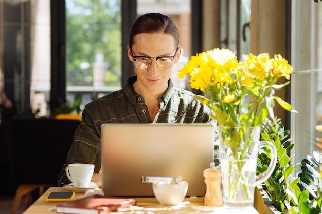 Praca na zlecenie. przystojny, inteligentny mężczyzna siedzi przy laptopie, koncentrując się na swojej pracy