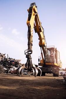 Praca na złomowisku i człowiek obsługujący przemysłową maszynę do podnoszenia,