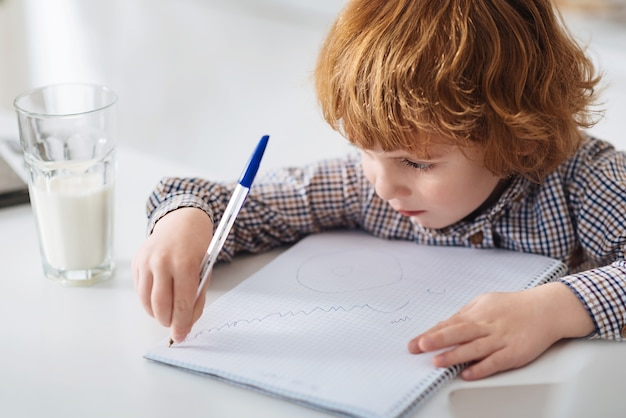Praca nad arcydziełem. skoncentrowany, bystry, uroczy dzieciak, używając swojego pióra, tworząc śmieszne zdjęcia w swoim notatniku, siedząc przy białym stole