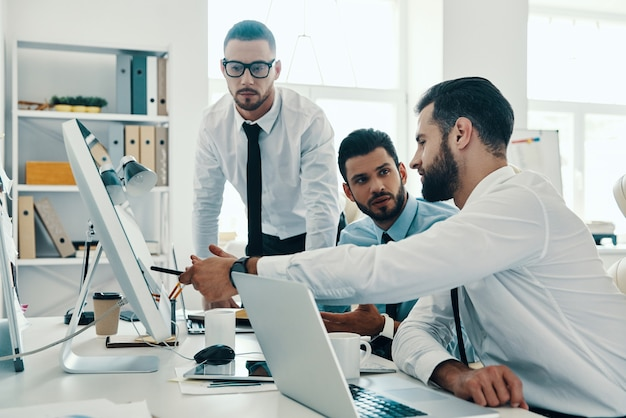 Praca nad niektórymi koncepcjami. grupa młodych, nowoczesnych mężczyzn w strojach formalnych, pracujących przy komputerach, siedząc w biurze