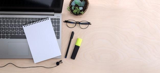 Praca online, edukacja lub freelancer. pusty notatnik na laptopie, mikrofon, okulary do monitora na drewnianym stole z miejsca na kopię.