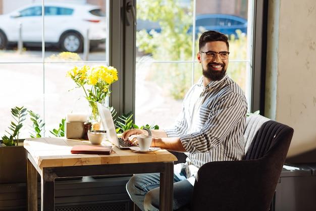 Praca online. radosny miły człowiek uśmiechający się podczas pracy z kawiarni na swoim laptopie