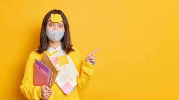 Praca podczas pandemii koronawirusa. zaskoczona azjatycka pracownica biurowa nosi maskę ochronną przyklejoną papierami, a samoprzylepne notatki wygląda zaskakująco wskazując na miejsce na kopię