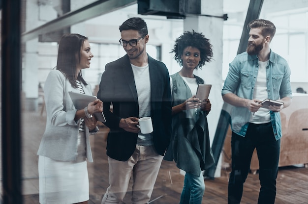 Praca poza granicami biurka. grupa młodych ludzi w eleganckim stroju casual