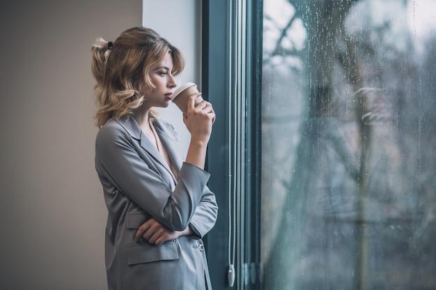 Praca, przerwa. profil zamyślonej młodej kobiety w garniturze picia kawy, stojąc w pobliżu dużego okna w biurze