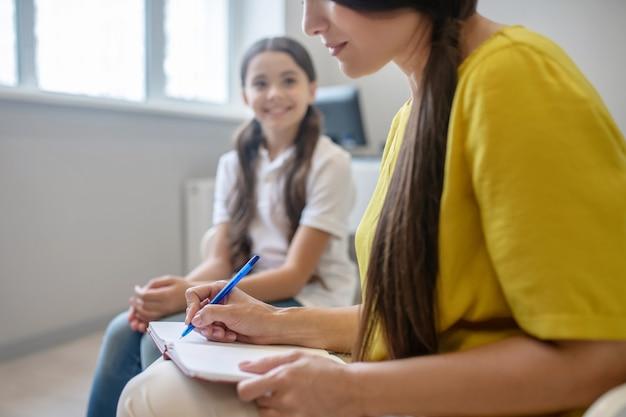 Praca psychologa. kobieta w żółtej bluzce pisania piórem w notesie i radosna dziewczyna siedzi w jasnym pokoju w ciągu dnia